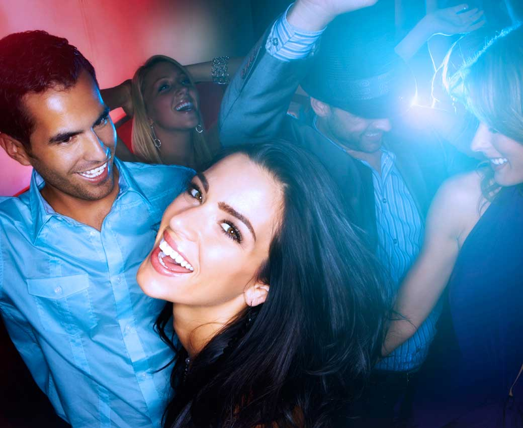 woman laughing, dancing with others at a club