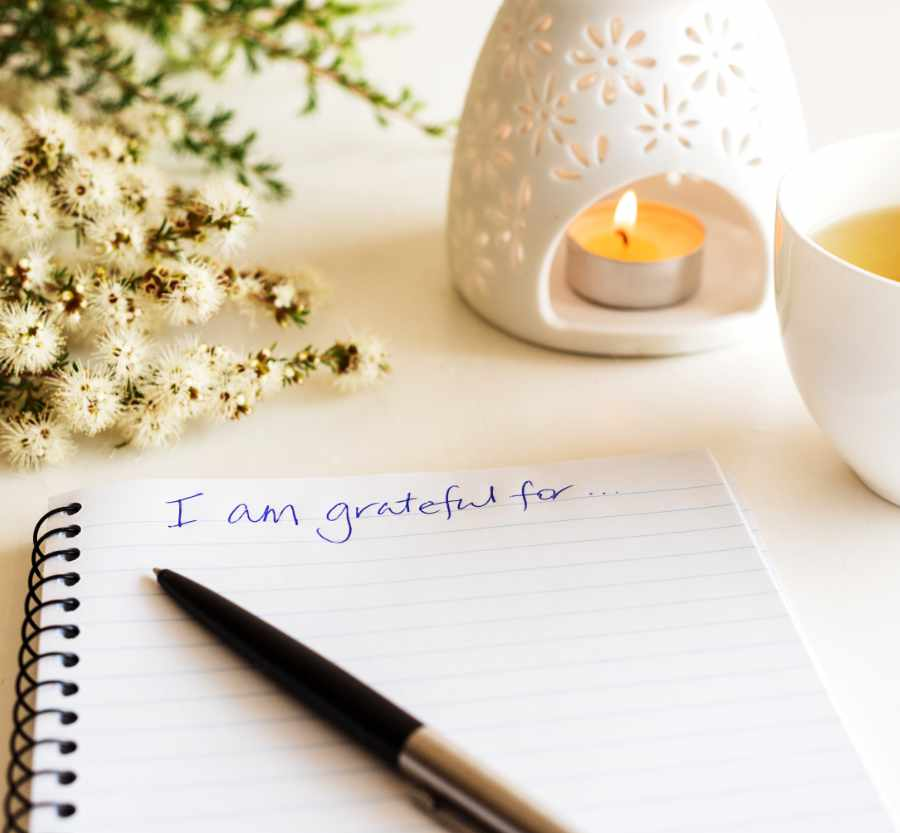 "An open journal with ""I am grateful for"" lies with a pen ready to write"