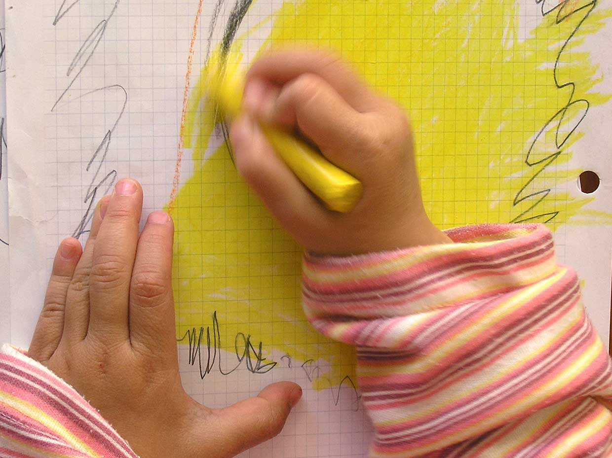 close-up of child hands scribbling with yellow marker