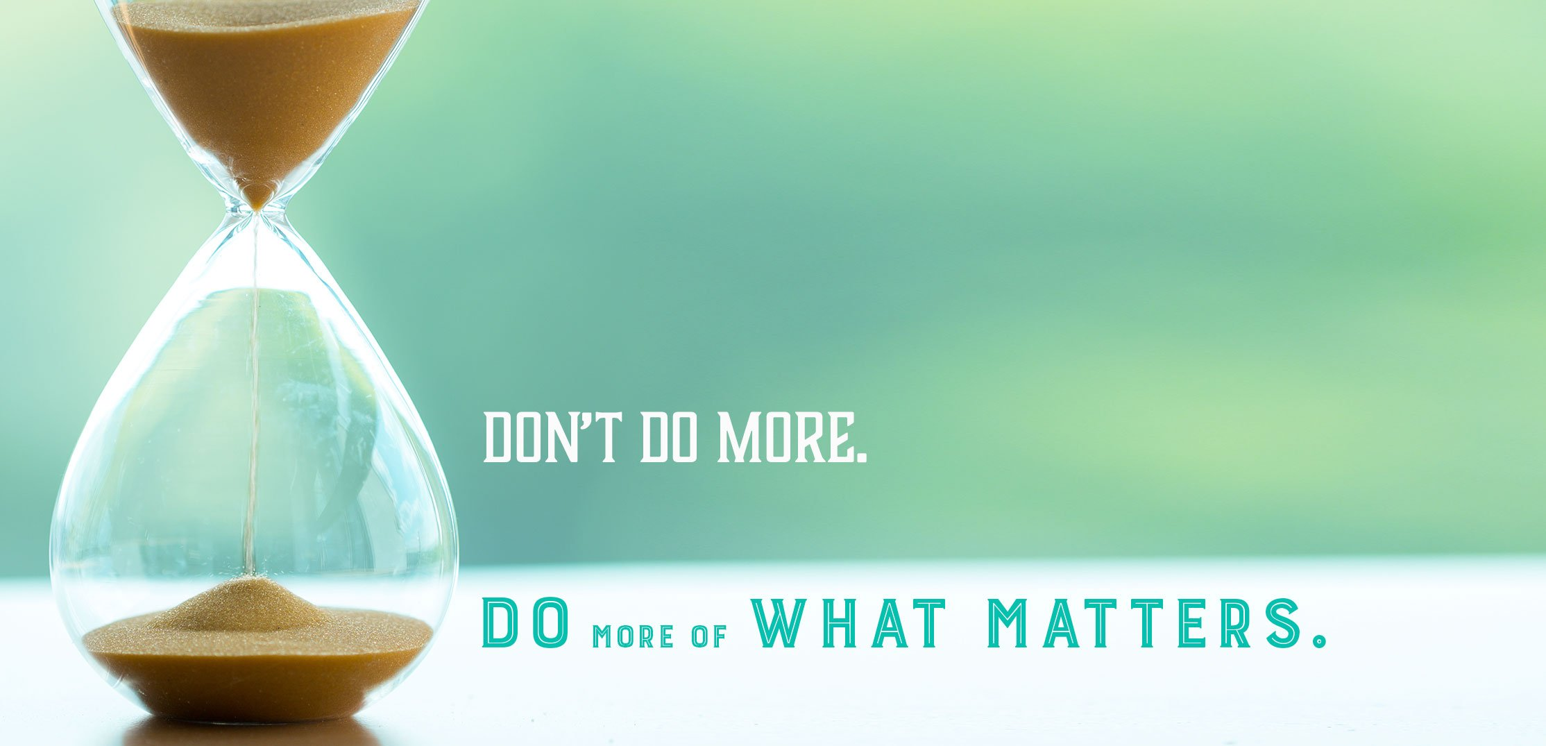 Close-up of hourglass with sand running on soft green background and sands with text saying Don't Do More, Do More of What Matters